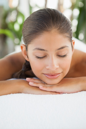 massage table: Beautiful brunette relaxing on massage table at a luxury spa