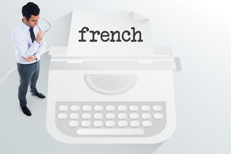 The word french and unsmiling businessman holding glasses against typewriter photo