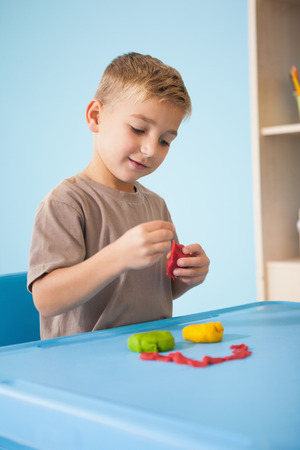 child's play clay: Cute little boy playing with modelling clay in classroom at the nursery school