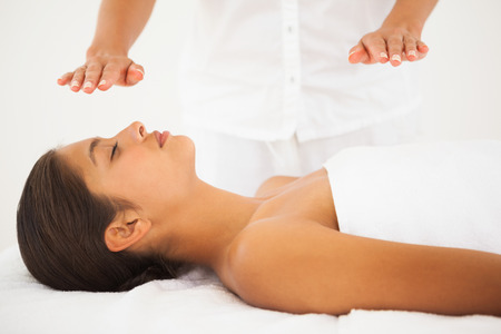 Beautiful brunette getting reiki therapy at the health spa photo