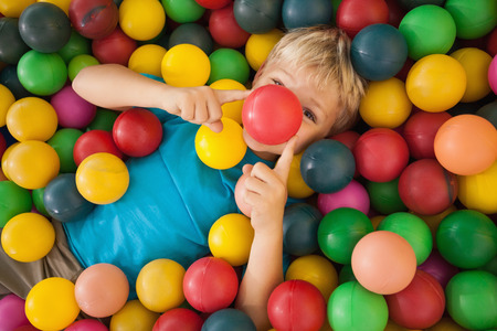 Happy boy playing in ball pool at a party photo