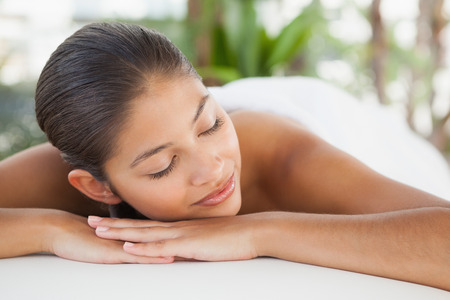massage table: Beautiful brunette relaxing on massage table at the health spa