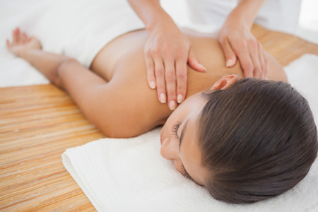 Beautiful brunette enjoying a shoulder massage at the health\ spa