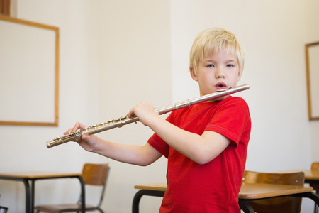 Cute pupil playing flute in classroom at the elementary school photo