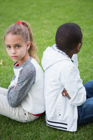 not talking: Young friends not talking to each other after fight in the park