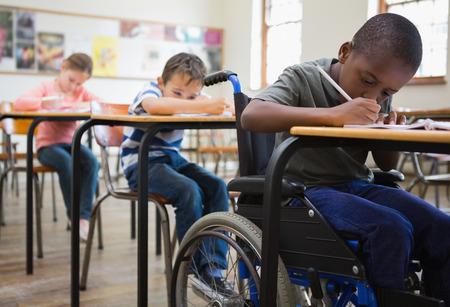 bambini pensierosi: Carino alunni che scrivono a banchi in aula presso la scuola elementare