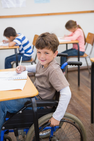 paraplegic: Disabled pupil writing at desk in classroom at the elementary school Stock Photo