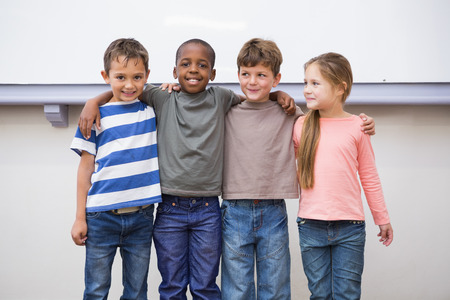 Classmates smiling at camera in classroom at the elementary school