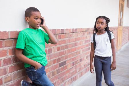 niños negros: Lindo alumno que habla en su teléfono inteligente en el pasillo en la escuela primaria