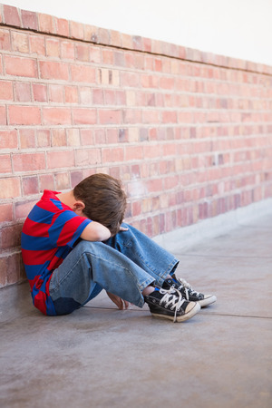 gloominess: Sad pupil sitting alone in corridor at the elementary school Stock Photo