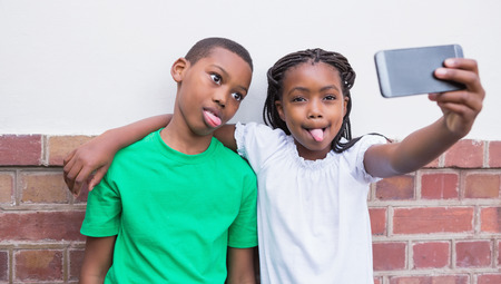 Cute pupils taking a selfie in the corridor at the elementary school photo