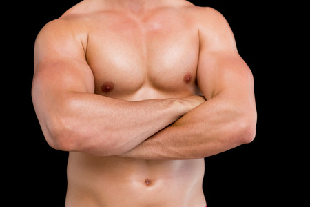 Close-up mid section of a shirtless muscular man with arms crossed over black background photo