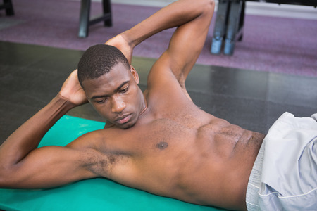 Side view of a shirtless muscular man doing abdominal crunches in gym photo