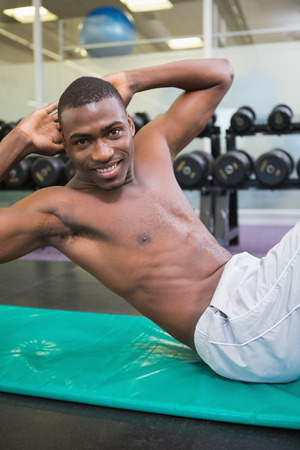 Side view portrait of a shirtless muscular man doing abdominal crunches in gym photo
