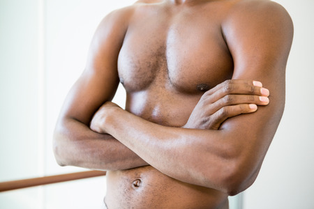 Close-up mid section of a shirtless muscular man with arms crossed in gym photo