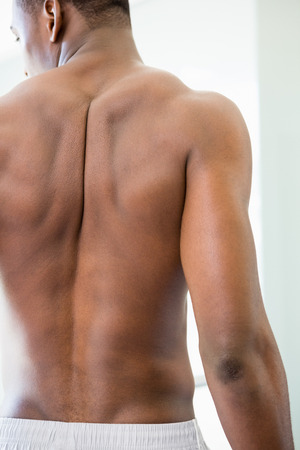 human back: Rear view of a shirtless muscular man standing in the gym