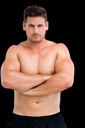 Portrait of a shirtless muscular man with arms crossed over black background photo