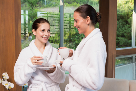 Two smiling young women in bathrobes having tea photo