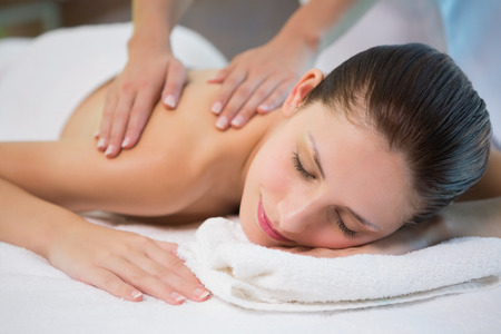 Close up of an attractive young woman receiving shoulder massage at spa center