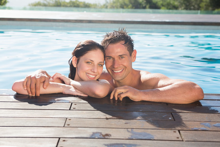 Portrait of a smiling young couple in swimming pool on a sunny day photo