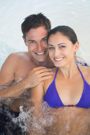 Close up portrait of a smiling young couple in swimming pool photo