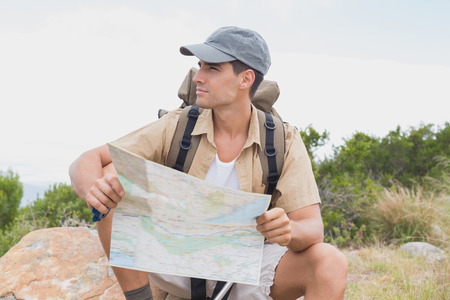 adventuring: Portrait of a hiking man sitting with map on mountain terrain Stock Photo