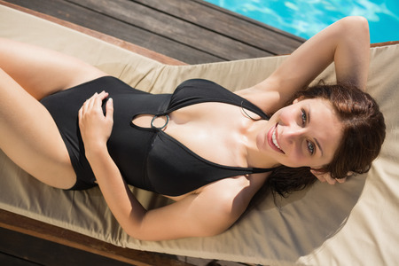 High angle view of beautiful young woman in bikini relaxing by swimming pool photo