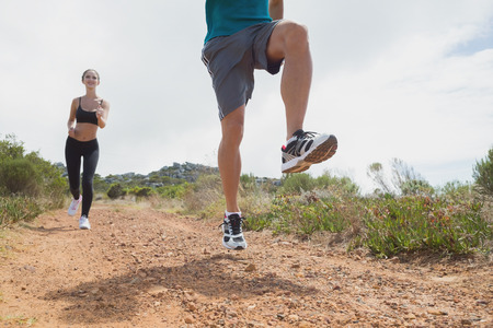 Low angle view of fit young couple running on countryside road photo