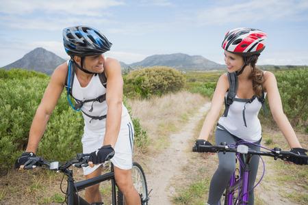 adventuring: Portrait of an athletic couple mountain biking Stock Photo