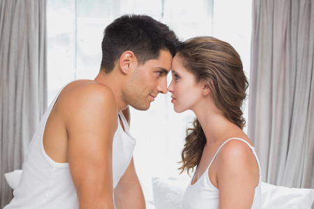 Side view of romantic young couple sitting in bed at home photo