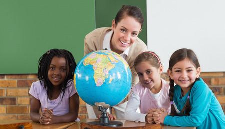 Cute pupils and teacher in classroom with globe  at the elementary school photo