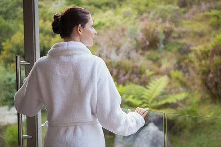 Rear view of a young woman wearing bathrobe against blurred plants photo