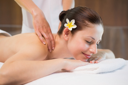 Side view of an attractive young woman receiving back massage at spa center photo