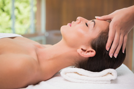 Side view of an attractive young woman receiving head massage\ at spa center
