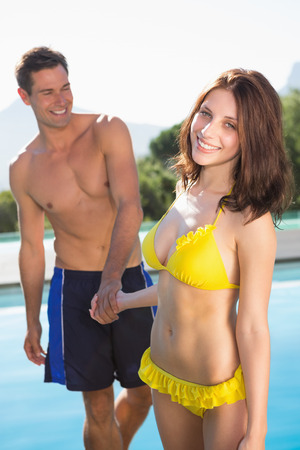 Happy romantic young couple holding hands by swimming pool on a sunny day photo