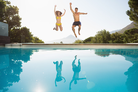 mid adult couple: Full length of a cheerful young couple jumping into swimming pool