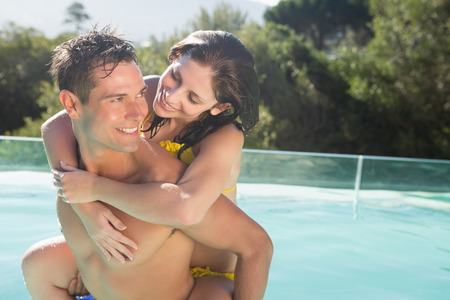 Smiling young man carrying cheerful woman by swimming pool on a sunny day photo