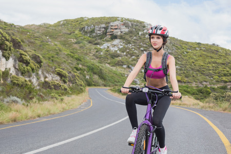 adventuring: Portrait of an athletic young woman mountain biking