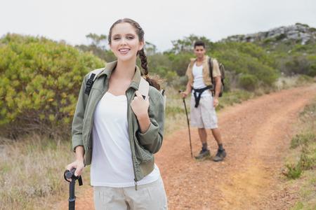 Portrait of hiking young couple walking on mountain terrain photo
