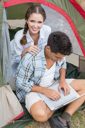 adventuring: Young couple using laptop in tent on countryside landscape