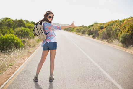 hitchhiking: Portrait of a pretty young woman hitchhiking on countryside road
