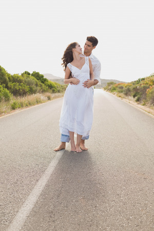 countryside loving: Full length of a loving young couple standing on countryside road