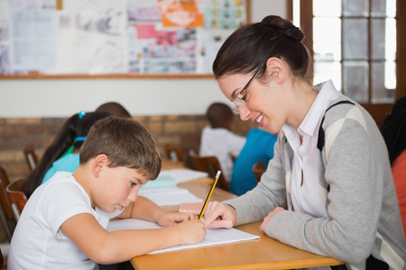 Pretty teacher helping pupil in classroom at the elementary school photo