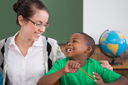 Cute pupil and teacher smiling at each other in classroom at the elementary school photo