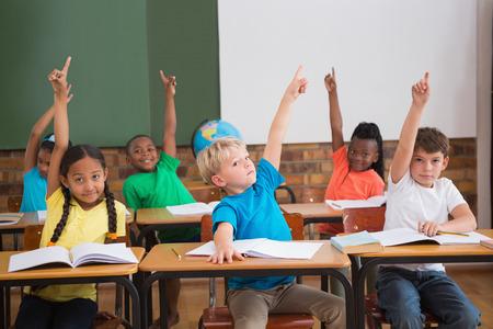 salon de clases: Alumnos lindos levantando las manos en la escuela primaria