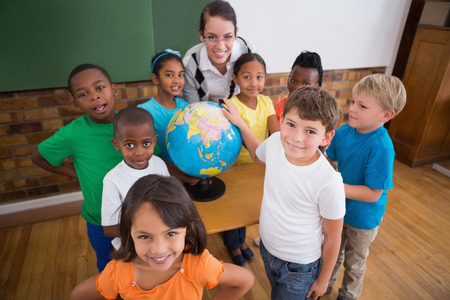 Cute pupils pointing to globe in classroom at the elementary school photo