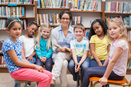 early childhood: Cute pupils and teacher reading in library at the elementary school Stock Photo