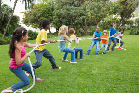 physical: Cute pupils playing tug of war on the grass outside  at the elementary school