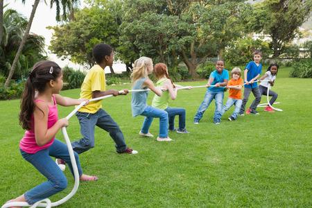 Leuke leerlingen die touwtrekwedstrijd spelen op het gras buiten op de lagere school