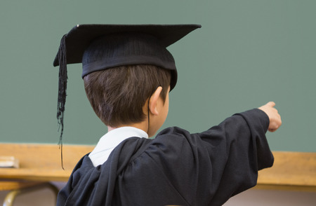 child learning: Cute pupil in graduation robe pointing in classroom at the elementary school Stock Photo